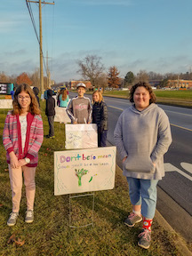 Students with anti-bullying signs in front of Creekside