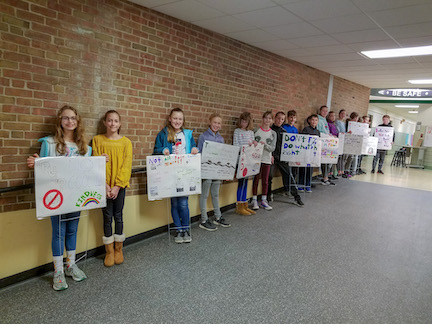 students in Creekside hallway with signs