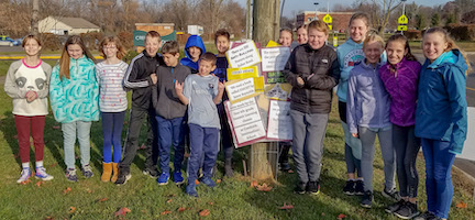 Creekside students line up along Baker Road with anti-bullying signs