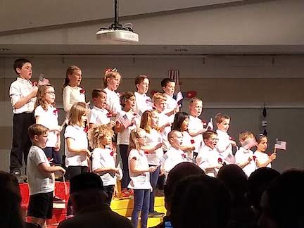 Students perform with flags at patriotic concert
